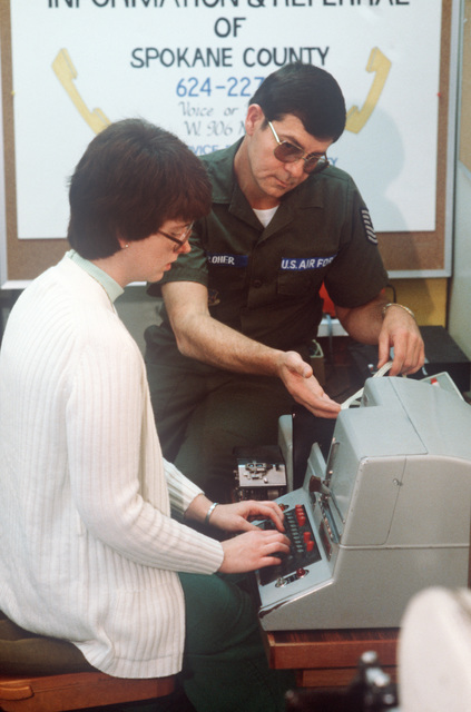 MASTER Sergeant (MSGT) Don Keroher of the 242nd Combat Communications Squadron discusses teletype procedures with Sue Koentopp, a senior counselor with the teletype service of the Spokane Library