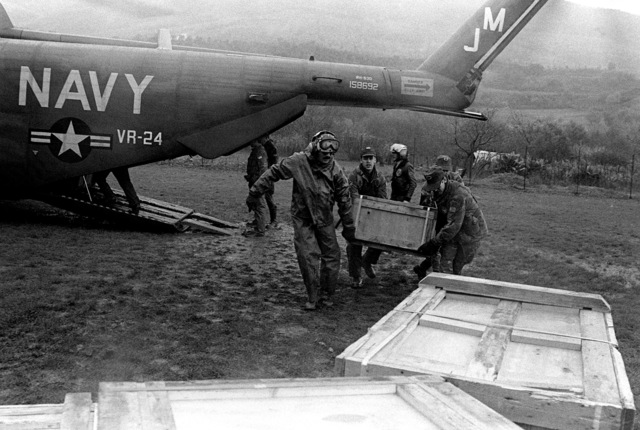 Navy and Army personnel offload relief supplies from a Navy RH-53D Sea Stallion helicopter after a major earthquake on November 23