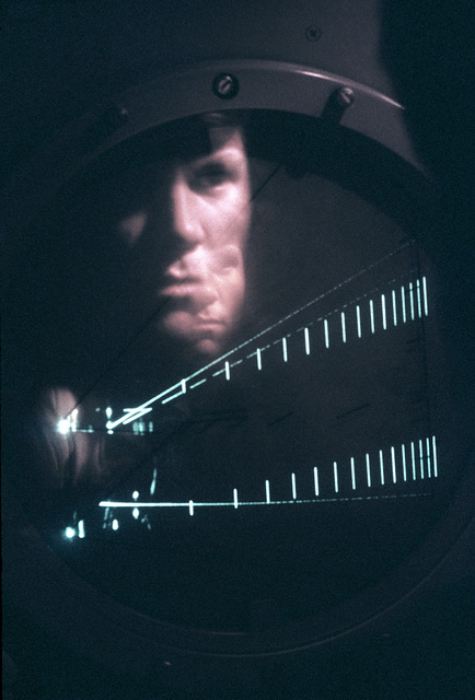 SRA James Calkins, an air traffic controller with the 1974th Communications Group of the Air Force Communications Command (AFCC), is reflected in the precision approach radar scope as he directs an aircraft