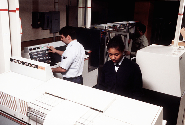 SRA John Thomas, automatic digital switching specialist, and SRA Debra Nixon, traffic analysis clerk, process incoming traffic at the Base Telecommunications Center, 1974th Communications Group, Air Force Communications Command (AFCC). Another enlisted man works in the background