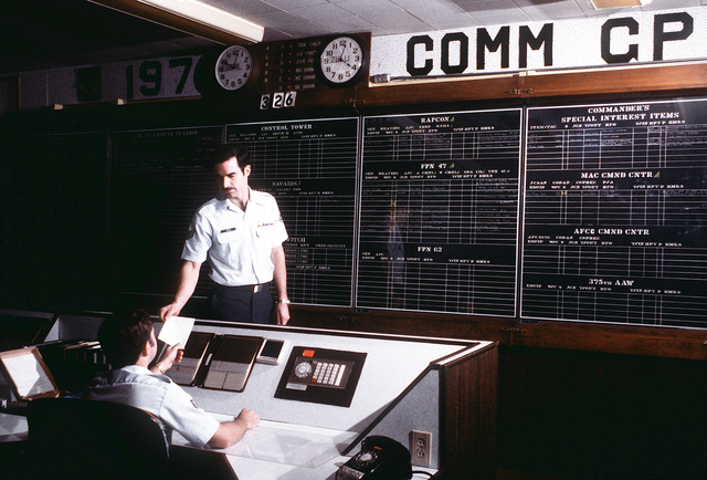 SSGT Larry Pierce, seated, passes repair project information to SSGT Jeff Duffield. Both men are job control technicians in the Job Control Section of the 1974th Communications Group, Air Force Communications Command (AFCC)