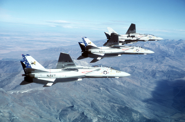 An air-to-air right side view of three F-14 Tomcat aircraft from Fighter Squadron 213 (VF-213) as they fly over the desert near NAS Fallon, Nevada