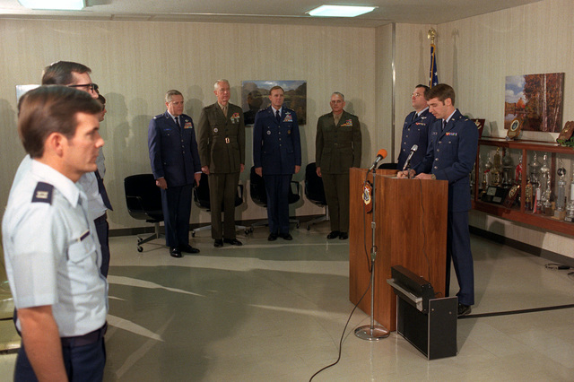 Deputy CHIEF of Public Affairs, 474th Air Base Wing, First Lieutenant Charles Merlo reads the Meritorious Unit Commendation Award citation. Behind him from left to right are: Colonel (COL)Duane Oberg, Major General (MGEN)Marc Moore, Lieutenant General (LGEN) William Ginn, LGEN Edward Bronars and COL Clarence Whiteside. The award was presented to the USAF Hospital. Yokota Air Base, Japan for the support by hospital personnel from 19-22 November 1979, given to the Marines burned in a fuel fire at Camp Fuji and subsequently airlifted to Brooks Army Burn Center, Texas