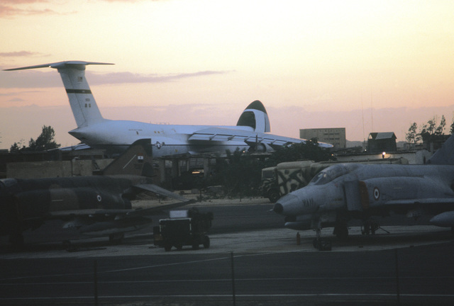 A C-5 Galaxy aircraft, in the background, waits ready for last minute loading at the conclusion of exercise Bright Star '80. In the foreground, two Egyptian F-4 Phantom II aircraft are parked