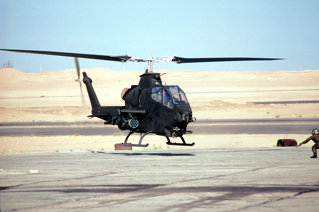 A left front view of an AH-1 Cobra helicopter landing after a mission during exercise Bright Star '80