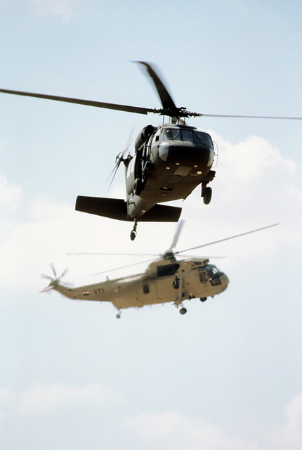 A UH-60 Black Hawk helicopter and an Egyptian H-3 Sea King helicopter transport news media personnel to an aerial firepower demonstration site during exercise Bright Star '80