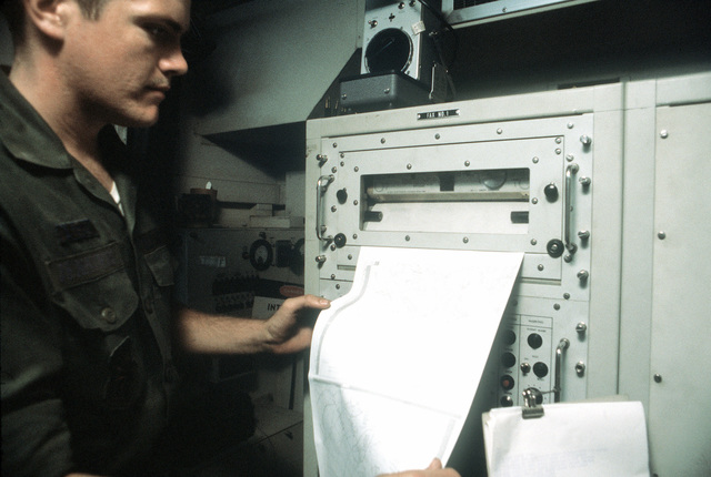 A1C Roger D. Jennings, 226th Combat Communications Squadron, Montgomery, Alabama, removes a global weather map from a weather receiver. The map will be used to keep pilots up to date on the weather changes during exercise Bright Star '80
