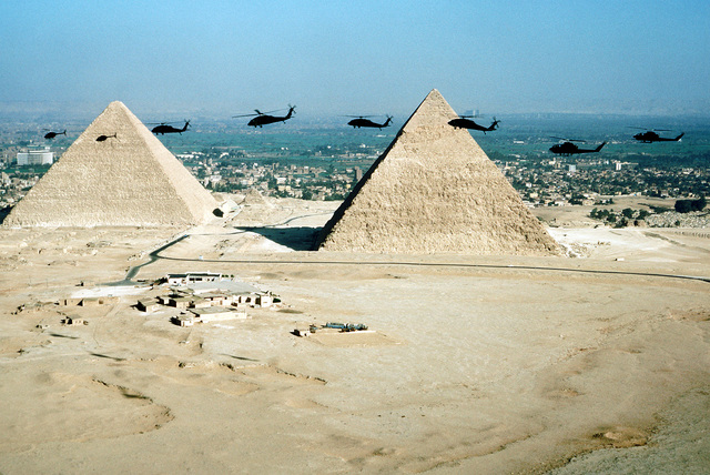 AN air-to-air left side view, from left to right, of two OH-58 Kiowa helicopters, four UH-60 Black Hawk helicopters and two AH-1 Cobra helicopters in front of two pyramids during exercise Bright Star '80