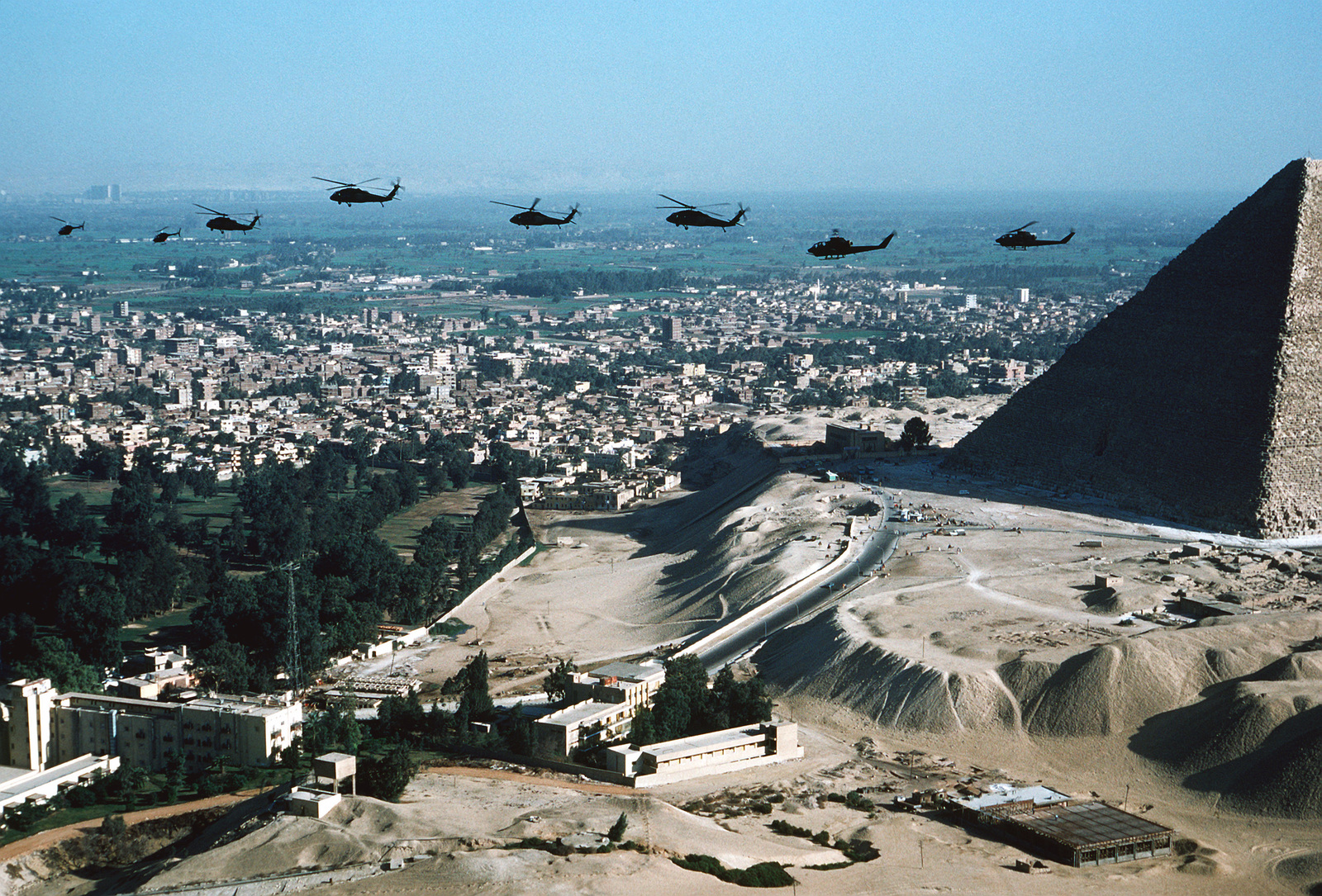 AN air-to-air left side view, from left to right, of two OH-58 Kiowa helicopters, four UH-60 Black Hawk helicopters and two AH-1 Cobra helicopters over the city during exercise Bright Star '80