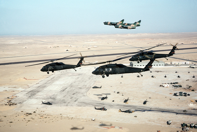 AN air-to-air view of three UH-60 Black Hawk (Blackhawk) helicopters and three camouflaged A-7 Corsair II aircraft over the airfield during exercise Bright Star '80