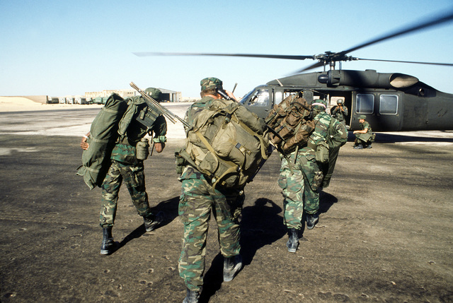 Forward air controllers carrying full field packs walk toward a waiting UH-60A Black Hawk helicopter from the 101st Aviation Battalion, Ft. Campbell, Kentucky. The men will be moved to a forward position to coordinate the air strikes during exercise Bright Star '80