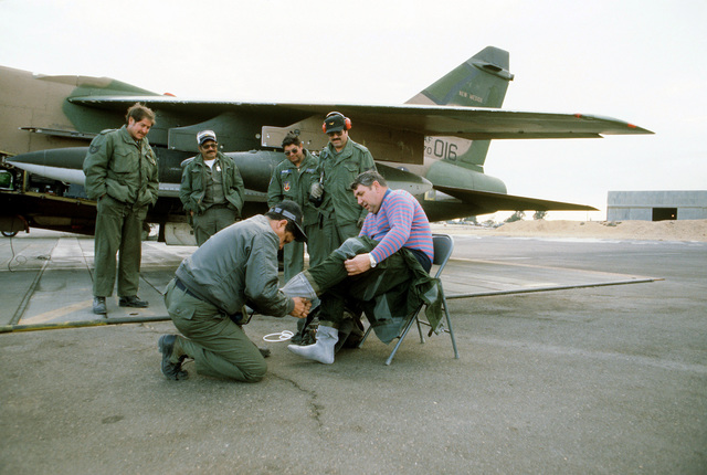 LTC James W. Vanscyoc, 150th Tactical Fighter Group, New Mexico Air National Guard, is helped into his anti-exposure suit before departure at the conclusion of exercise Bright Star '80