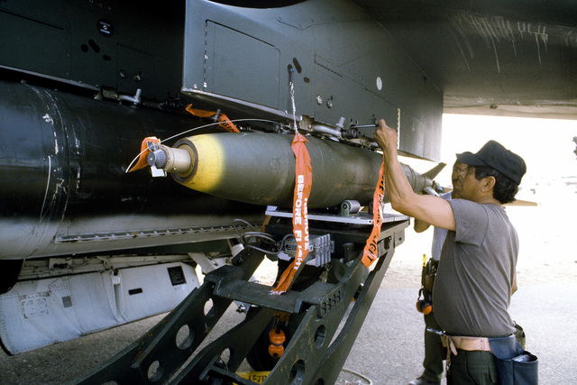 MSGT Dan Lopez and TSGT Gary F. Summerbell, 150th Tactical Fighter Group, load a Mark 82 bomb onto an A-7 Corsair II aircraft during exercise Bright Star '80