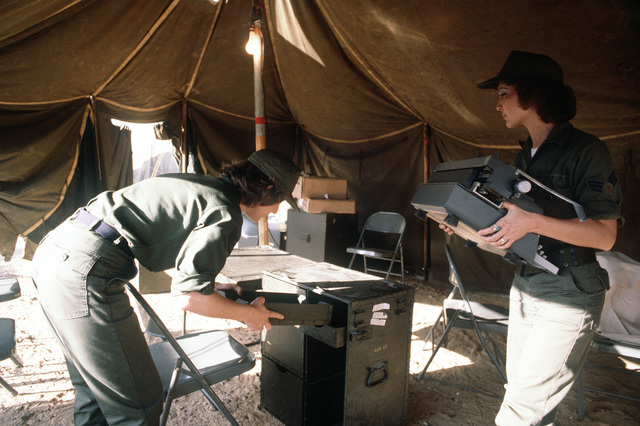 SENIOR AIRMAN Janice D. McCarely, an administrative specialist with the 226th Combat Communications Squadron, carries a typewriter to her desk as SGT. Wilma L. Walls organizes her area in the field office they will use during exercise Bright Star '80