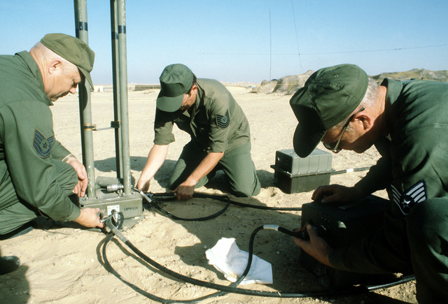 SSGT Clyde A. Hanson, TSGT Eddie E. Brown and MSGT Don V. Stanfield install the frequency control head on a mobile antenna during exercise Bright Star '80
