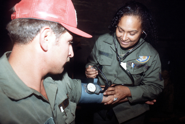TSGT Marline J. Hobbs, 188th Tactical Fighter Group, checks the blood pressure of SSGT A. Sieminski, 820th Civil Engineering Squadron, during sick-call at the field hospital. They are participating in exercise BRIGHT STAR '80