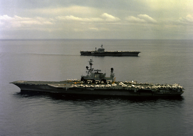 An aerial port beam view of the aircraft carrier USS MIDWAY (CV 41), and a starboard beam view of the aircraft carrier USS CONSTELLATION (CV 64) in the background