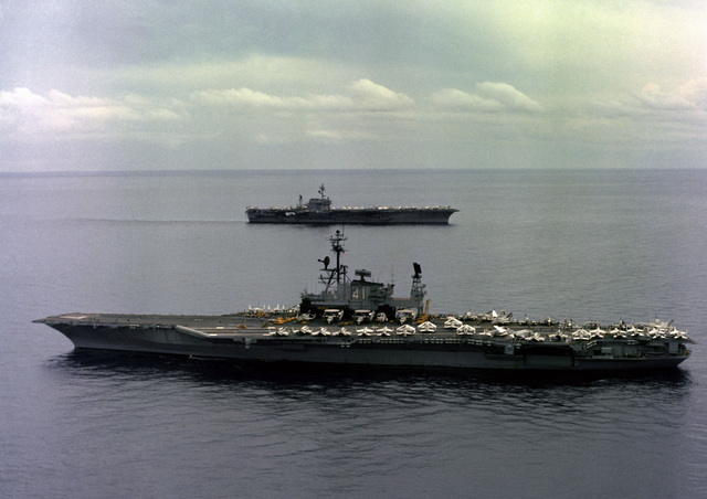 An aerial port beam view of the aircraft carrier USS MIDWAY (CV 41) and starboard beam view of aircraft carrier USS CONSTELLATION (CV 64), in the background