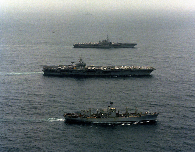 An aerial port starboard beam view, from front to back, of the combat stores ship USS MARS (AFS 1), the nuclear-powered aircraft carrier USS DWIGHT D. EISENHOWER (CVN 69) and the of the aircraft carrier USS MIDWAY (CV 41) underway