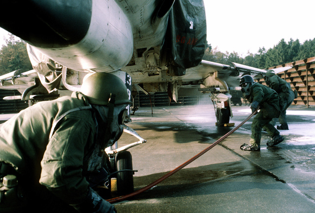A disaster preparedness team dressed in chemical warfare gear performs decontamination maintenance on an F-4E Phantom II aircraft during the chemical warfare exercise Salty Mace. The team is assigned to the 50th Civil Engineering Squadron