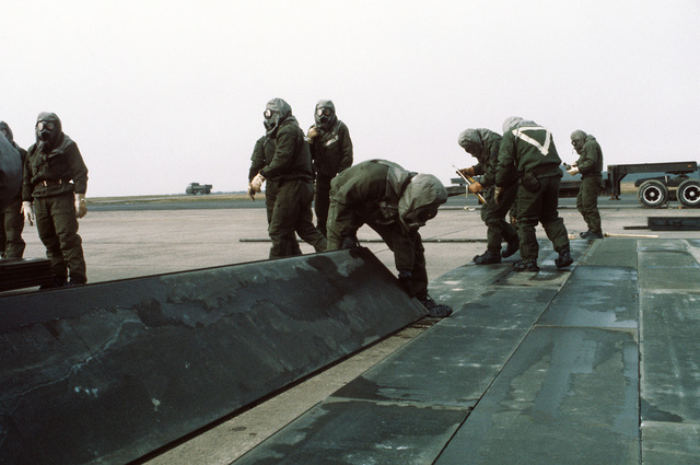 Members of the 50th Civil Engineering Squadron dressed in chemical warfare gear repair a simulated bomb crater during the chemical warfare exercise Salty Mace