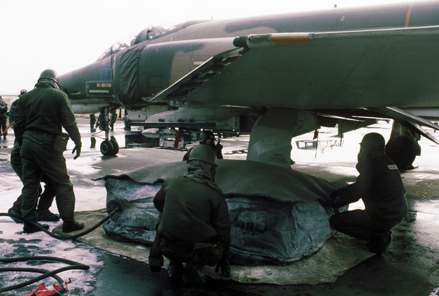 Members of the 50th Civil Engineering Squadron repair a simulated flat tire of an F-4E Phantom II aircraft during the chemical warfare exercise Salty Mace