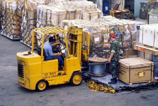 A Navy enlisted man and AMN Raymond Haug use a forklift to lift a pallet of cargo during Operation Deep Freeze '80