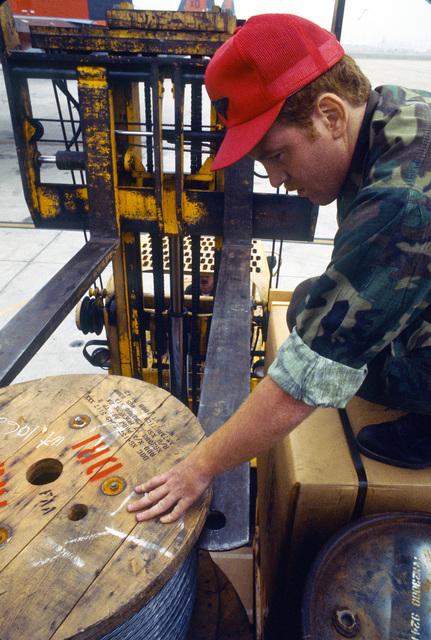 AMN Raymond Haug, a rigger of the 63rd Aerial Port Squadron, positions a spool of wire onto a pallet with the help of a forklift operator during Operation Deep Freeze '80