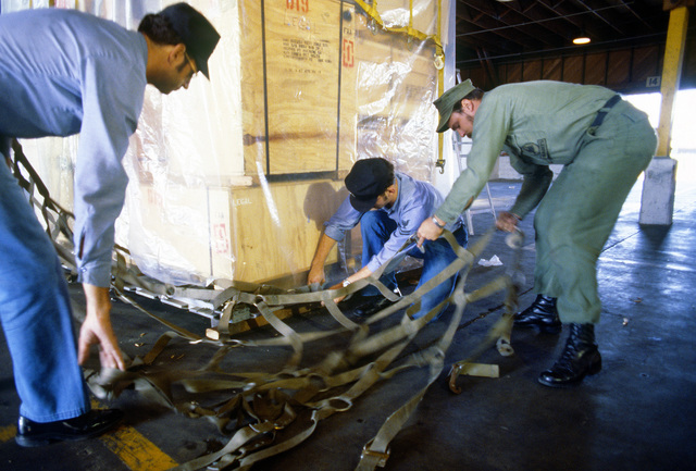Navy and Army enlisted personnel put palletizing webbing over a pallet being readied for shipment to McMurdo Station, Antarctica, during Operation Deep Freeze '80