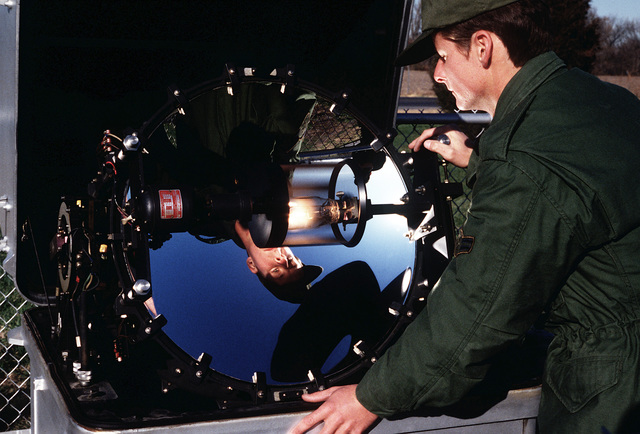A1C Robert Carson, weather equipment repair specialist with the 1974th Communications Group of the Air Force Communications Command (AFCC), checks the operation of the cloud height detector at the end of the runway