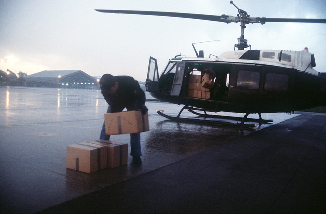 An Army UH-1H Iroquois helicopter is unloaded at Capodichino Airport. The helicopter is carrying relief supplies for victims of a major earthquake