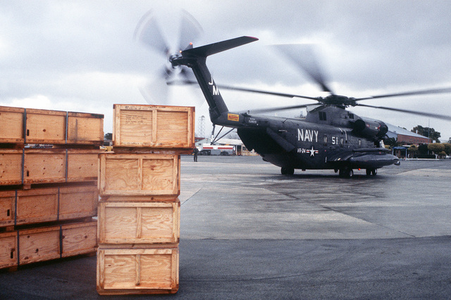 Right side view of a Navy RH-53D Sea Stallion helicopter from Fleet Logistics Support Squadron 24 taxiing to the runway. The helicopter is carrying relief supplies for rural victims of a major earthquake