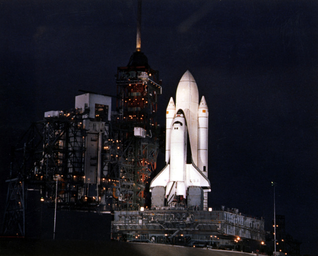 A night view of the Space Transportation System (STS) shuttle Columbia on Launch Pad 39. The shuttle is being prepared for its first flight