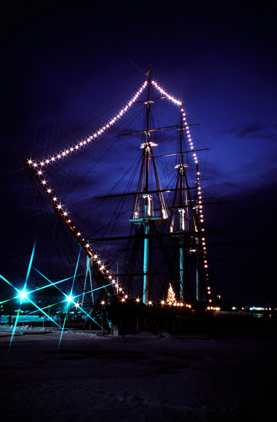 A view of the sail frigate USS CONSTITUTION (IX-21) decorated with lights and a Christmas tree from the holiday. A star lens was used to obtain the dramatic lighting effect