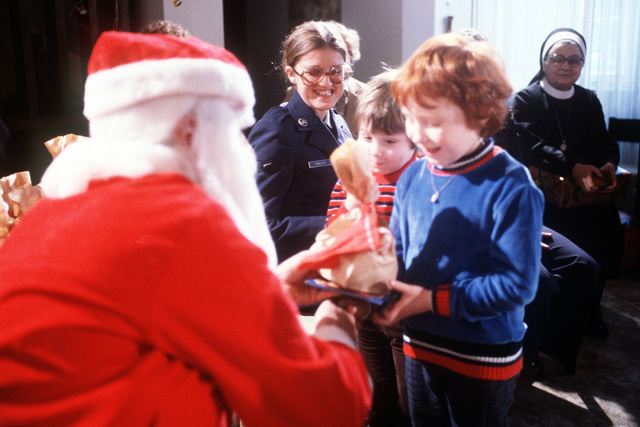 "AMN May Kowalczyk, center, from the 36th Supply Squadron, smiles as children from Irminen Orphanage receive bags of gifts from ""Santa,"" TSGT John Quigley, during the Christmas party given by the squadron"
