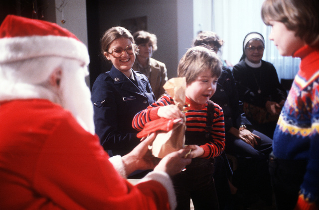 "AMN May Kowalczyk, left, from the 36th Supply Squadron, smiles as children from Irminen Orphanage receive bags of gifts from ""Santa,"" TSGT John Quigley, during the Christmas party given by the squadron"