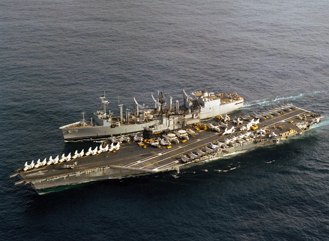 An aerial port beam view of the aircraft carrier USS MIDWAY (CV 41) and the replenishment oiler USS KALAMAZOO (AOR 6) preparing for underway replenishment operations