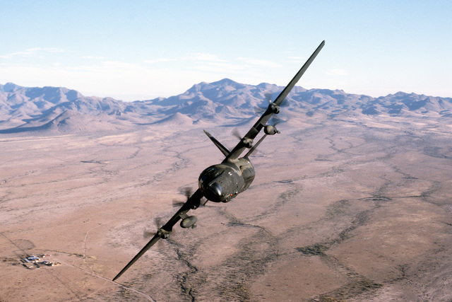 AN air-to-air front view of an MC-130E Hercules aircraft banking to the right over the Arizona desert. The aircraft is assigned to the 8th Special Operations Squadron at Hurlburt Field, Fla
