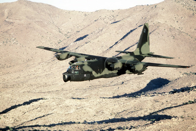 AN air-to-air front view of an MC-130E Hercules aircraft flying low-level maneuvers over the Arizona desert. The aircraft is assigned to the 8th Special Operations Squadron at Hurlburt Field, Fla