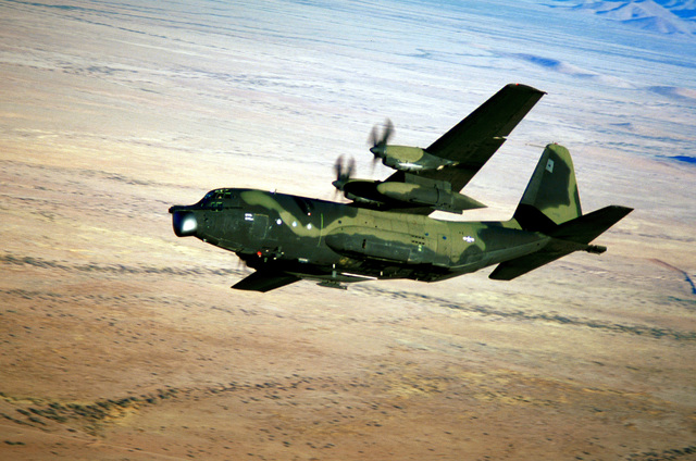 AN air-to-air left side view of an MC-130E Hercules aircraft banking to the right while flying low-level maneuvers over the Arizona desert. The aircraft is assigned to the 8th Special Operations Squadron at Hurlburt Field, Fla