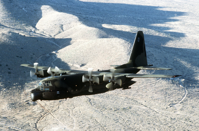 AN air-to-air left side view of an MC-130E Hercules aircraft flying low-level maneuvers over the Arizona desert. The aircraft is assigned to the 8th Special Operations Squadron at Hurlburt Field, Fla
