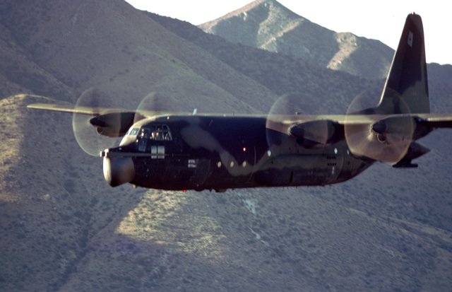 AN air-to-air left side view of an MC-130E Hercules aircraft flying low-level maneuvers over the Arizona desert. The aircraft is assigned to the 8th Special Operations Squadron at Hurlburt Field, Florida