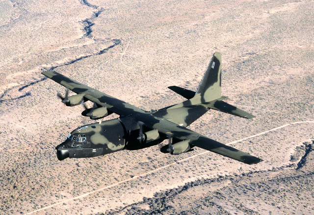 AN air-to-air view of an MC-130E Hercules aircraft flying low-level maneuvers over the Arizona desert. The aircraft is assigned to the 8th Special Operations Squadron at Hurlburt Field, Fla