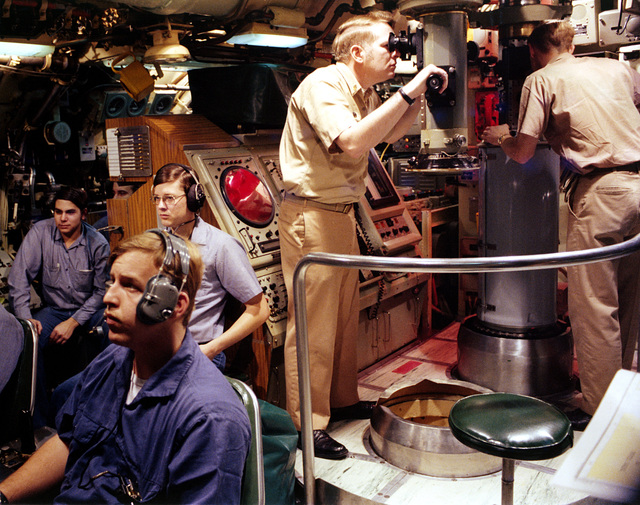 An officer aboard a Sturgeon class nuclear-powered attack submarine uses the ship's periscope in the control room