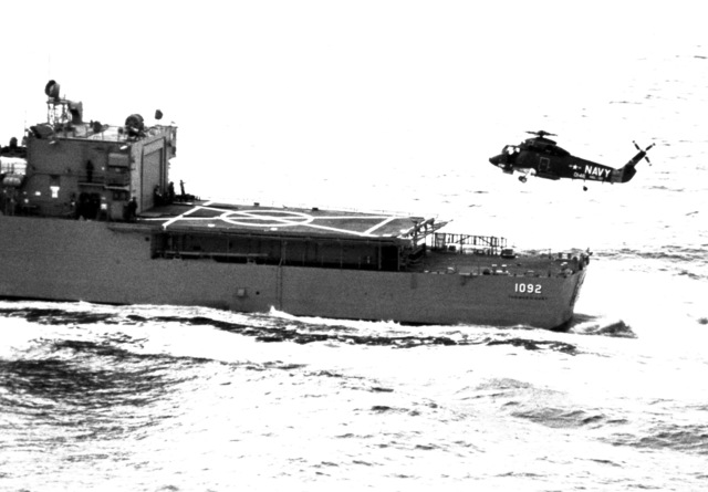 Left side view of an SH-2F Seasprite Mark 1 Light Airborne Multi-Purpose System (LAMPS) helicopter, in flight over the stern of the frigate USS THOMAS C. HART (FF-1092)