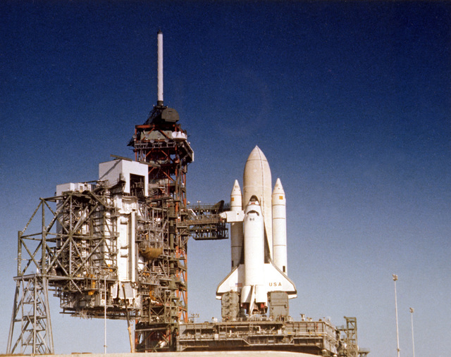 The Space Transportation System (STS) shuttle Columbia, with access arms in place, at Launch Pad 39. The shuttle is undergoing preparations prior to its maiden flight