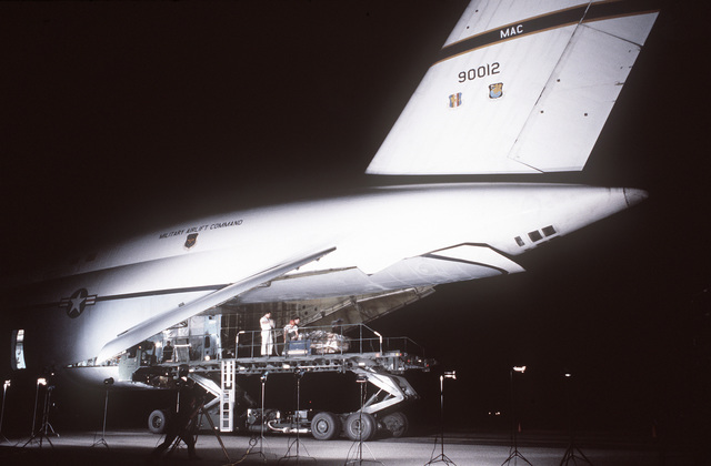 A left rear view of a C-5A Galaxy aircraft from Travis Air Force Base, California, being loaded with cargo by members of the 374th Aerial Port Squadron. The aircraft is participating in Project Diego Garcia airlift operations