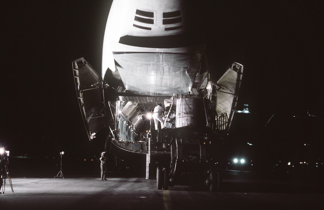 A rear view of a C-5A Galaxy aircraft from Travis Air Force Base, California, being loaded with cargo by members of the 374th Aerial Port Squadron. The aircraft is participating in Project Diego Garcia airlift operations