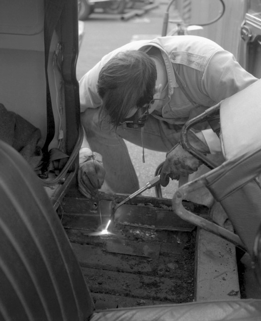 An auto hobby shop worker welds a rust spot along the frame of his car