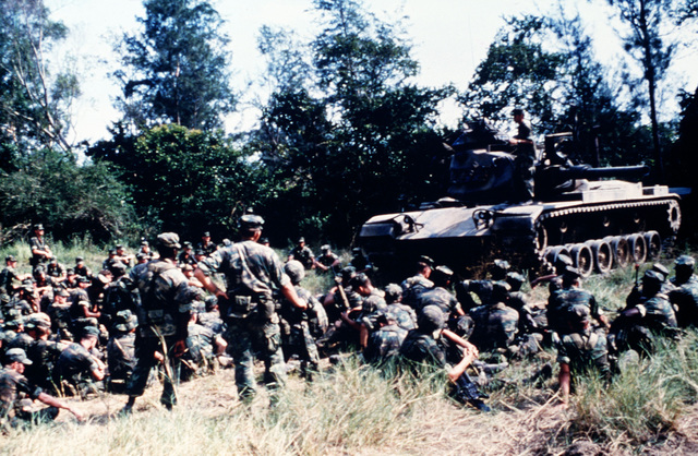 Marine Corps infantrymen of Company B, 1ST Battalion, 3rd Marines, 3rd Marine Division, Fleet Marine Force, sit on the ground around a M60A1 tank. The crewmen of the tank, from the 1ST Marine Division, Fleet Marine Force, conduct classes on the nomenclature of the tank